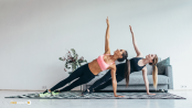 two ladies in a pilates full side plank exercise. both in leggings and crop tops on a blcak and white rug with a grey sofa chair behind them.